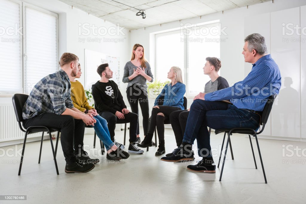 Young woman sharing problems in group therapy Young woman discussing problems with friends and mental health professional. Social worker is with young university students in lecture hall. They are in group therapy at university. 18-19 Years Stock Photo