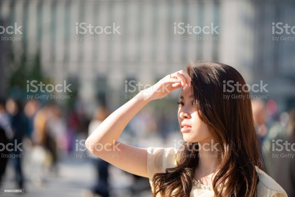 太陽から彼女の目をシールドする若い女性の輝き ストックフォト