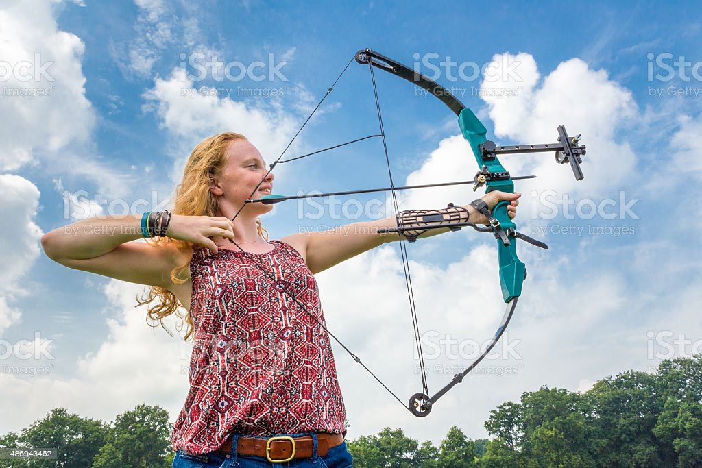 Young woman shooting archery with compound bow and arrow stock photo