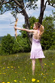 Young woman is standing in the tall grass and aiming with a bow.See some similar pictures from my portfolio: