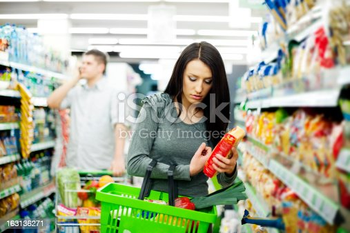istock A young woman shopping at a supermarket with others nearby 163136271