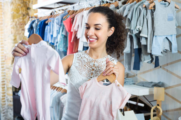 young woman shopping baby sleepers stock photo