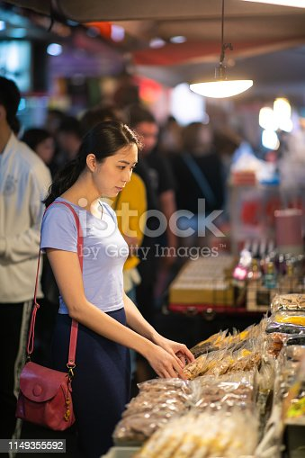 Young woman shopping dry fruit at night market in Taipei