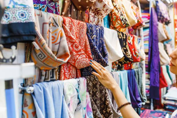 젊은 여성이 새로운 스카프를 쇼핑 하 고 바자르에서 화려한 직물을 선택 - 바자 뉴스 사진 이미지