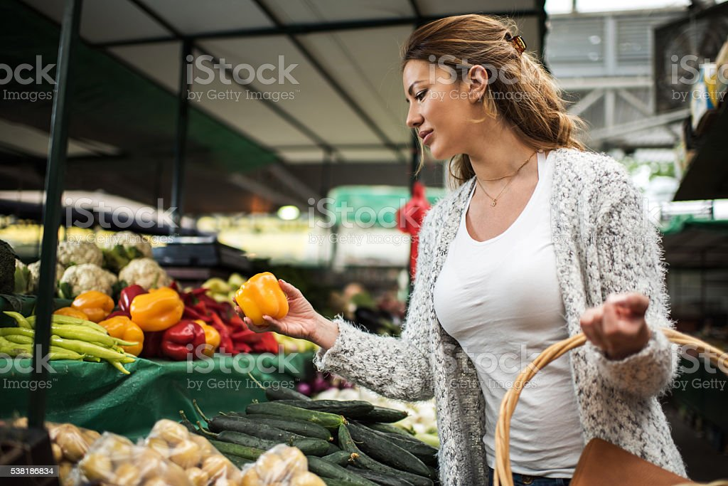 Young woman shopping for groceries on farmer's market. stock photo