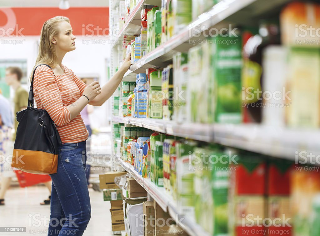 Young woman shopping for juice in supermarket stock photo