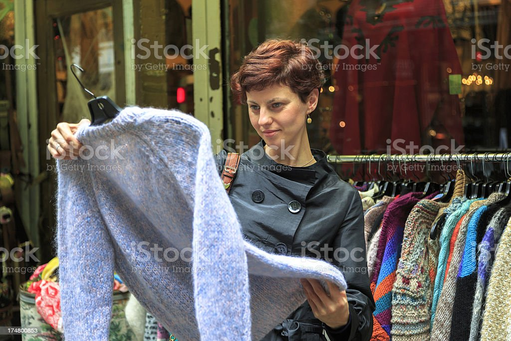 Young woman shopping for vintage clothing stock photo