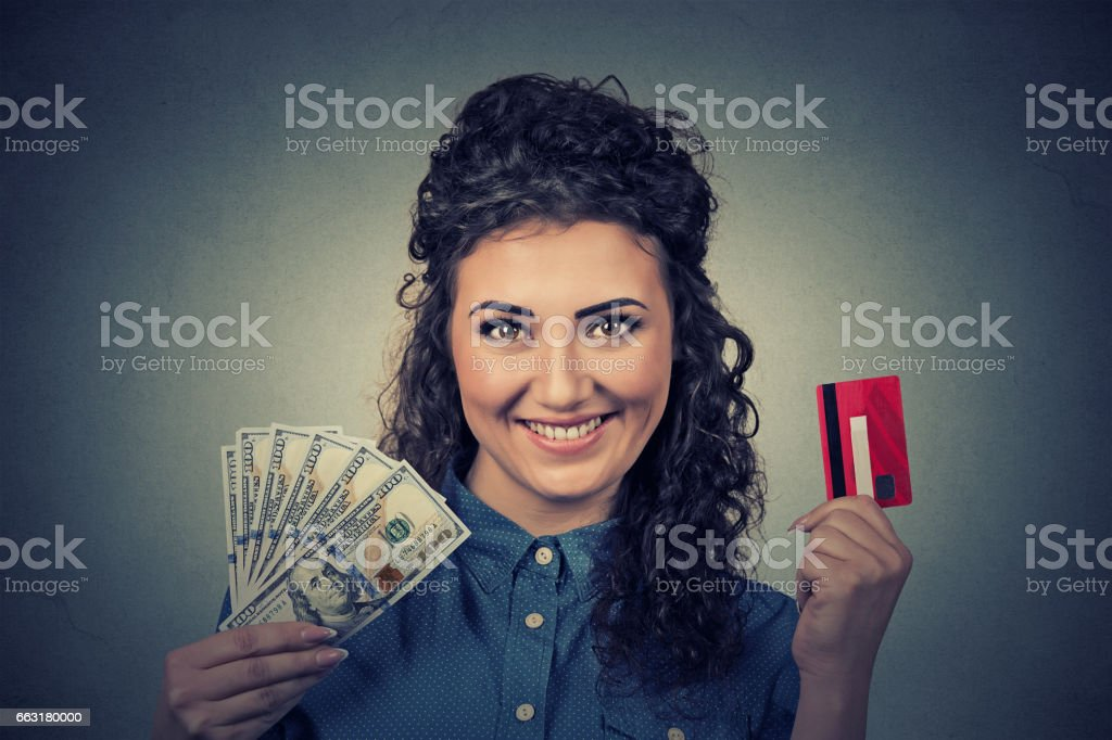 Young woman shopping holding showing credit card and cash dollar banknotes bills stock photo