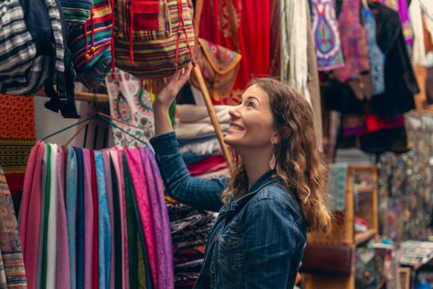 giovane donna shopping in un bazar - bazar mercato foto e immagini stock