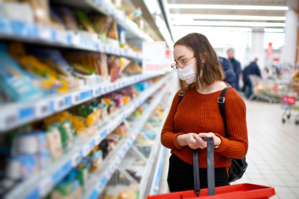 young woman shopping in a grocery store and wearing protective medical mask - shopping стоковые фото и изображения