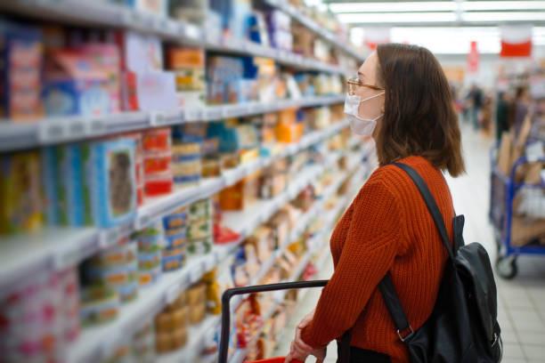 Junge Frau beim Einkaufen in einem Lebensmittelgeschäft und trägt schützende medizinische Maske – Foto