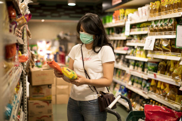Young woman shopping in a grocery store and wearing protective medical mask stock photo