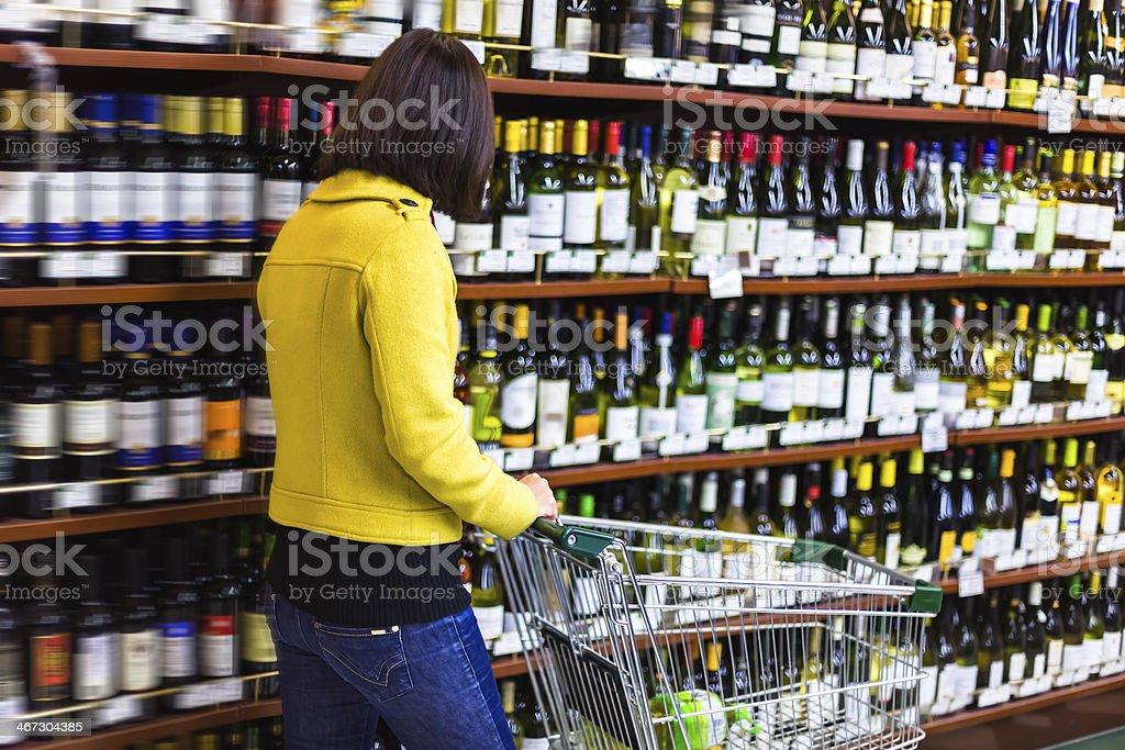 Junge Frau Einkaufen im Supermarkt, Wein in den Regalen – Foto