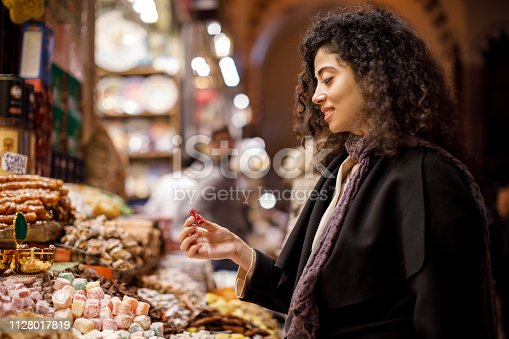 Young woman shopping in turkish delight shop in Grand Bazaar, Istanbul, Turkey