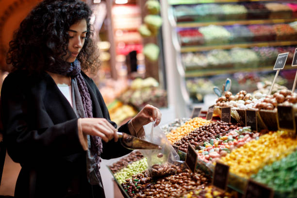 Young woman shopping in turkish delight shop in Grand Bazaar, Istanbul, Turkey stock photo