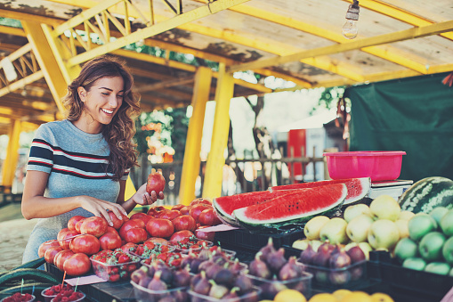 istock Young woman shopping on the farmer's market 613104682