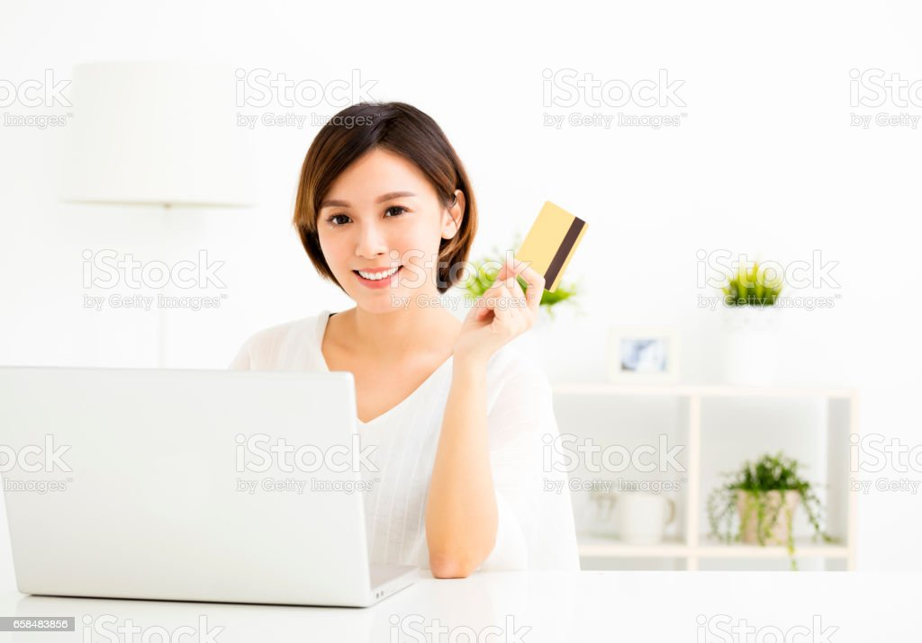 young woman shopping online and paying with  credit card stock photo