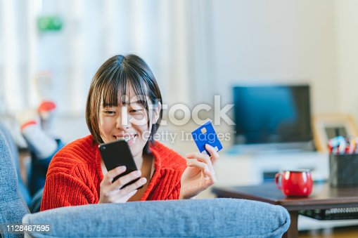 A young woman is shopping online at home.
