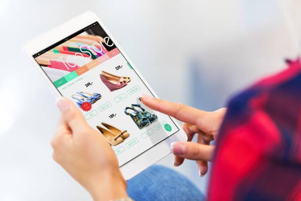 young woman shopping online on tablet computer - online shopping imagens e fotografias de stock