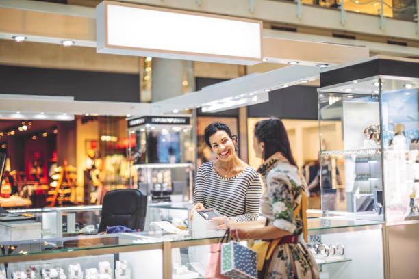 junge frau shopping - uhrenshop stock-fotos und bilder