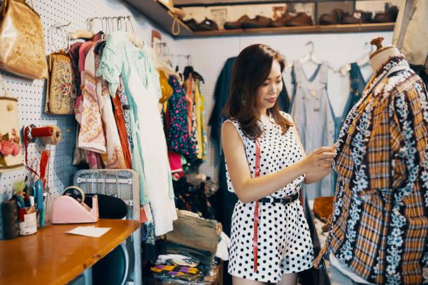年輕女子在老式服裝店購物 - small business saturday 個照片及圖片檔