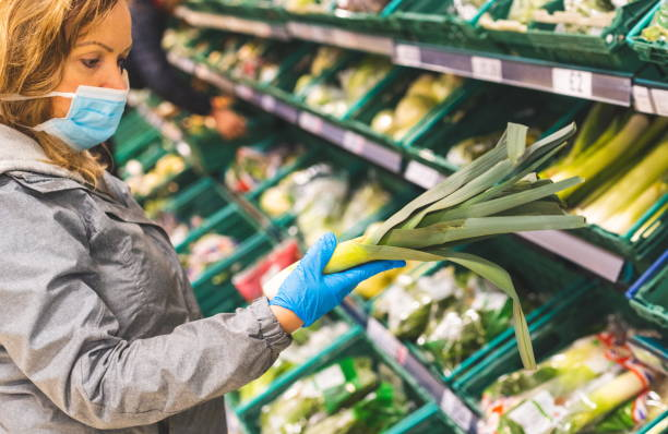 Young Woman shopping wearing mask and gloves panic buying. Self isolating and self distancing during pandemic. Shopper buying healthy vegetables during coronavirus pandemic. covid-19 virus pandemic. stock photo