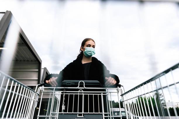 Young woman shopping with corona virus face mask pushing shopping cart stock photo
