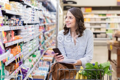 istock Young woman shops in dairy section of grocery store 871227790