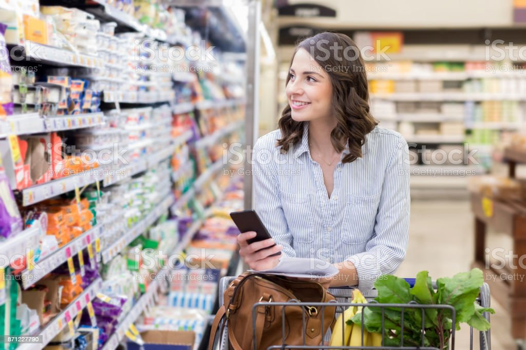 Young woman shops in dairy section of grocery store stock photo