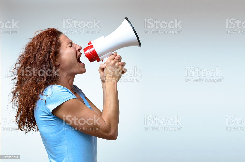 Young woman shouting into a megaphone stock photo