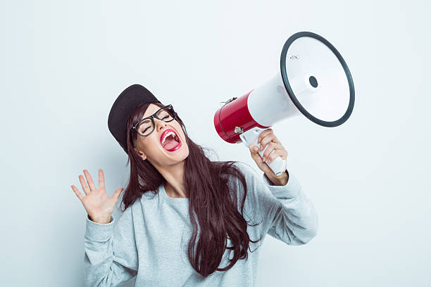 Young woman shouting into megaphone stock photo