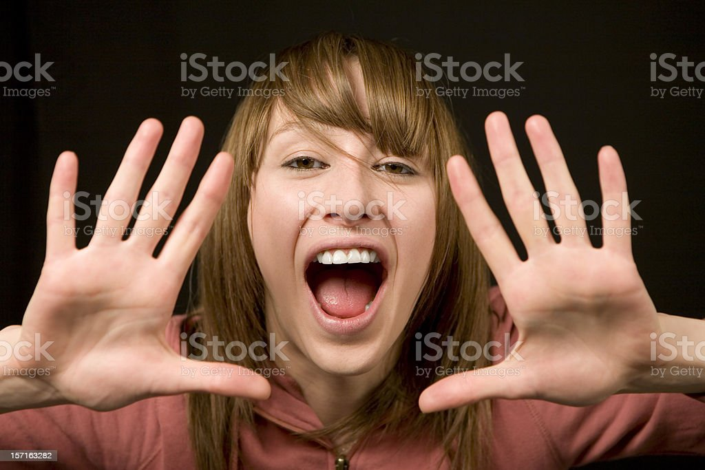Young woman shouting through her hands stock photo
