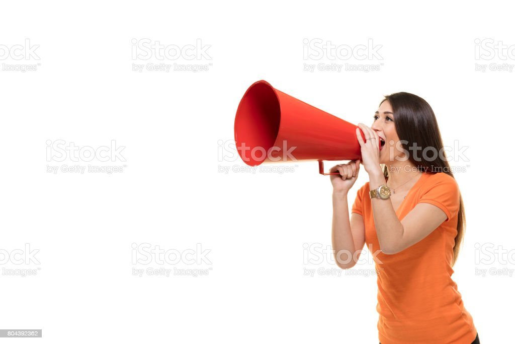 Young woman shouts into a megaphone. Young woman shouts into a megaphone. 20-29 Years Stock Photo