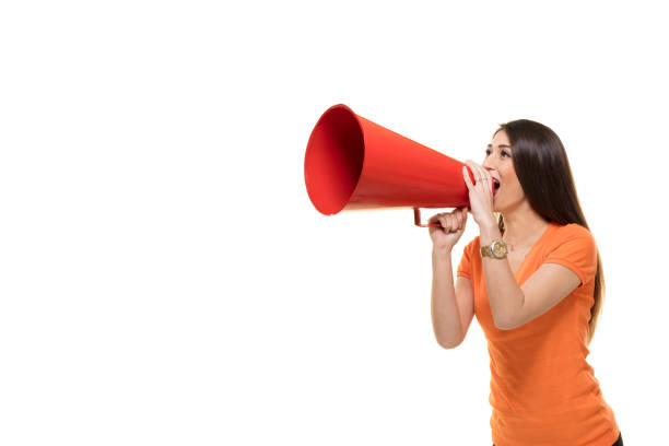 young woman shouts into a megaphone. - battle of the sexes concept stock pictures, royalty-free photos & images
