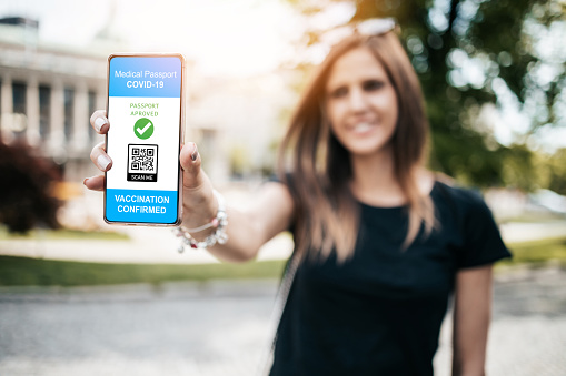 Happy and positive young adult woman holding smart phone with electronic Covid-19 immunity passport. Modern technology and pandemic prevention concept.