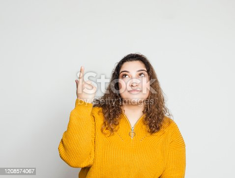 istock Young woman showing aside ad advert product copy space isolated over gray background 1208574067