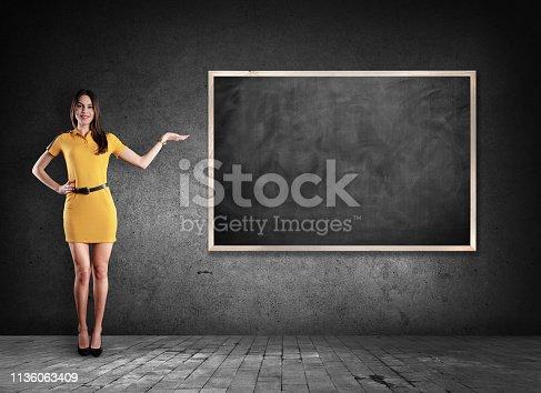 485083346 istock photo Young woman showing blackboard 1136063409