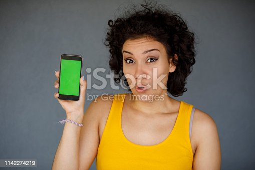 1132512623istockphoto Young woman showing cell phone with green screen 1142274219