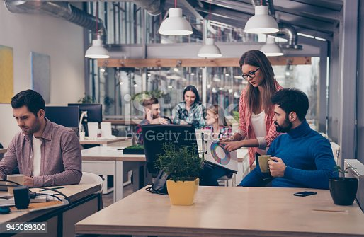 istock Young woman showing diagrama of growth to her colleague 945089300