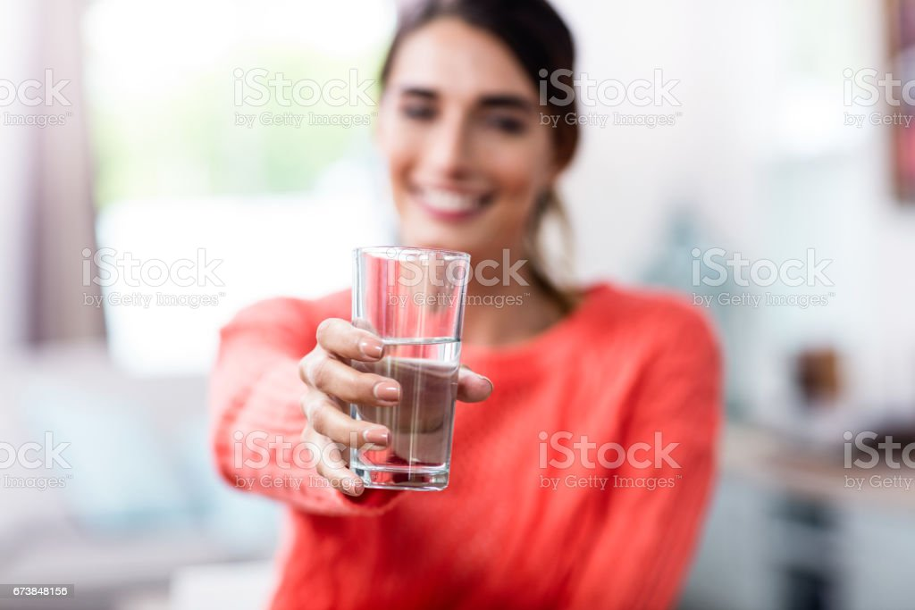 Young woman showing drinking glass with water