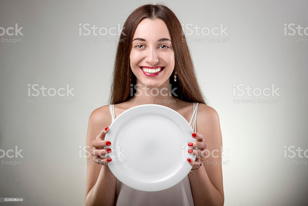 Young woman showing empty plate. stock photo
