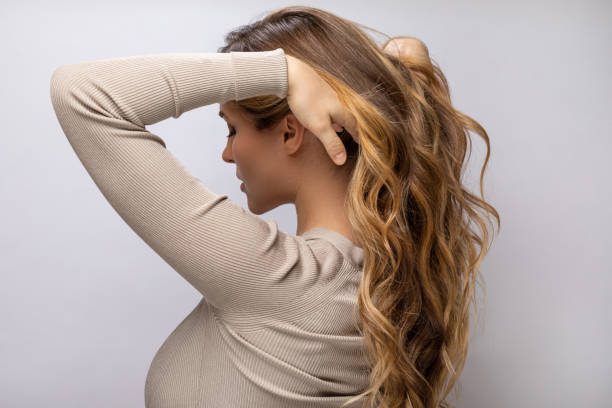Young woman showing her beautiful hair after dyeing and styling stock photo