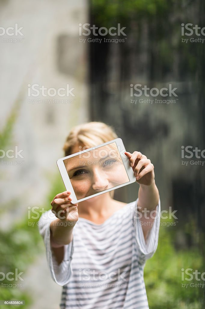 Young woman showing photograph on digital tablet stock photo