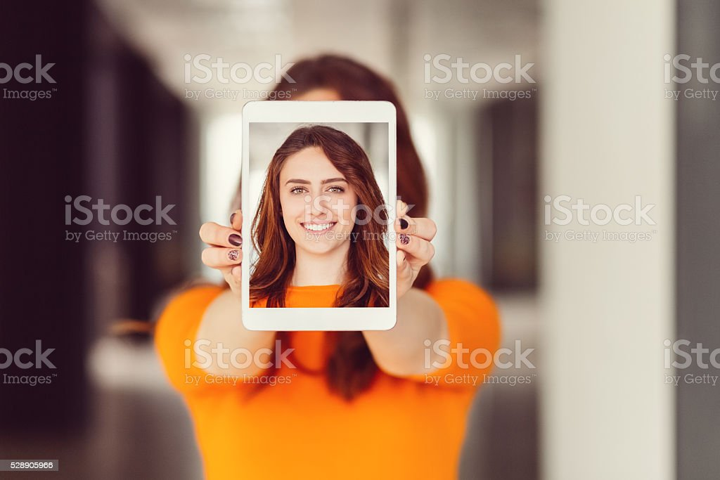 Young woman showing self portrait on tablet pc stock photo