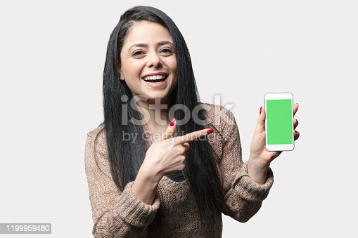 1132512623istockphoto Young woman showing smartphone screen over gray background very happy pointing with hand and finger 1199959480