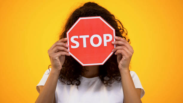 jonge vrouw toont stopteken, protesteren tegen racisme en geweld, bewustwording - avondklok stockfoto's en -beelden