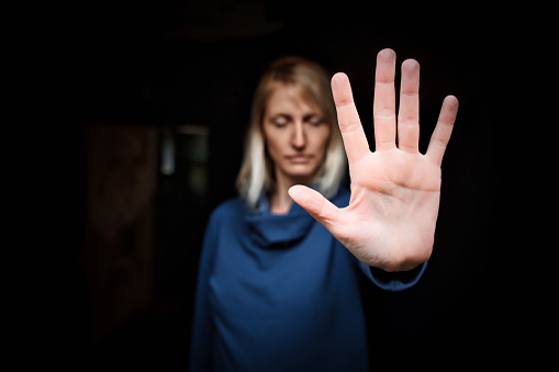 Close-up of a young woman making a stop gesture. Focus on foreground