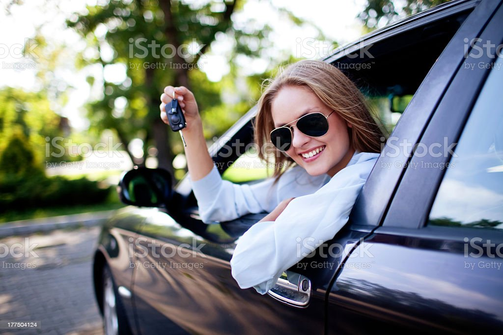 Young woman showing the keys to her new car stock photo