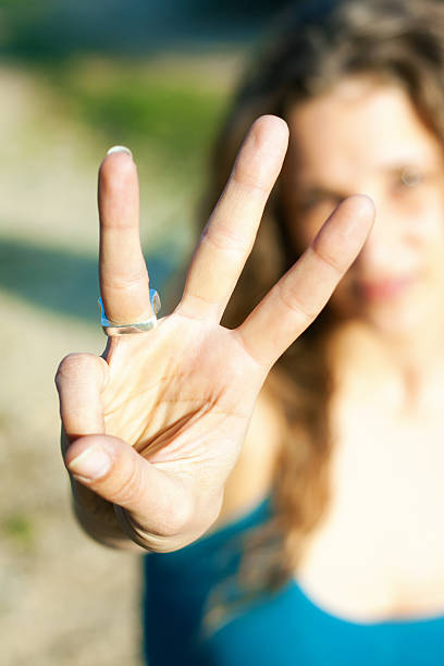 young woman showing three fingers to the camera stock photo