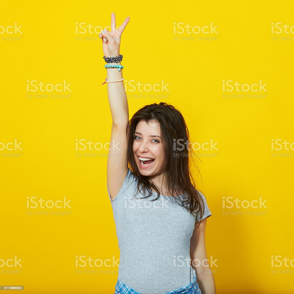 Young woman showing two fingers on yellow background stock photo